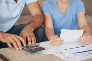 Close-up mid section of a couple with bills and calculator at home